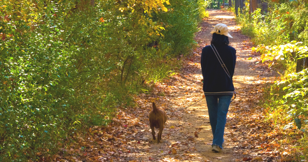Picture of dog mom with pup on trail in Raleigh, North Carolina in the fall